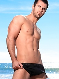 Brock Cooper posing naked by the sea